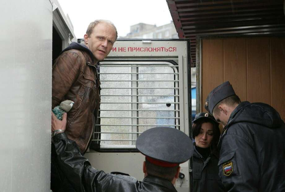 IRussian photographer Denis Sinyakov  is escorted to a court room in Murmansk, Russia. The court in the northern Russian city of Murmansk jailed 28 Greenpeace activists who protested last week near the platform owned by the Russian state energy giant, Gazprom. Photo: Igor Podgorny, Associated Press