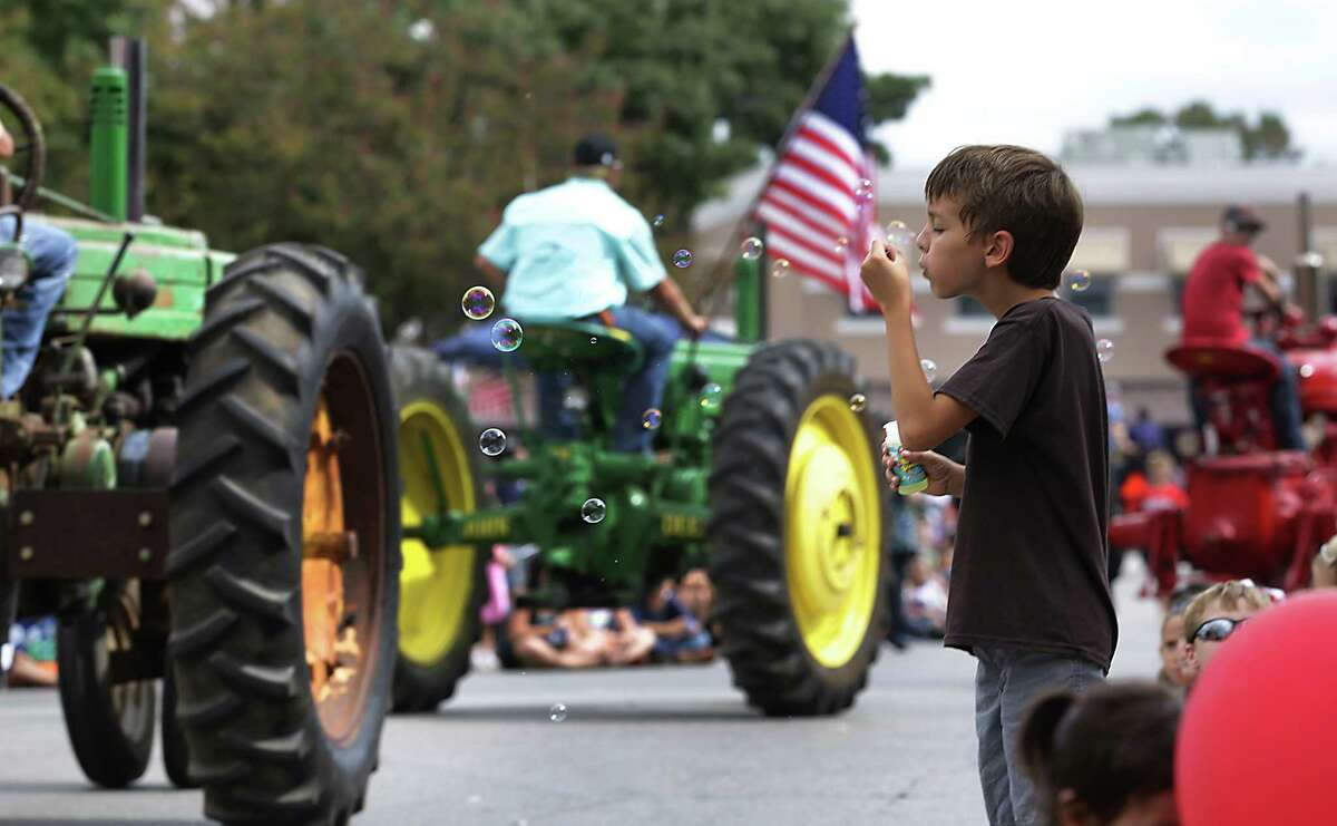 Hunter Fontaine, 9 yr. old, blows bubbles as a long line of tractors roll down San Antonio St. during the Comal County Fair Parade through the center of New Braunfels, on Friday, Sept. 27, 2013.