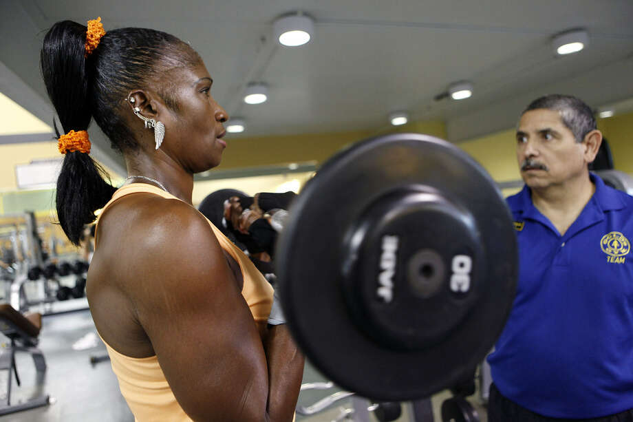 Shirley Bates, 52, works out  with trainer Anthony Rodriguez  at Gold's Gym on Austin Highway. Bates has lost more than 100 pounds since 2011 and now shows off the transformation in physique competitions. Photo: Cynthia Esparza / For The Express-News