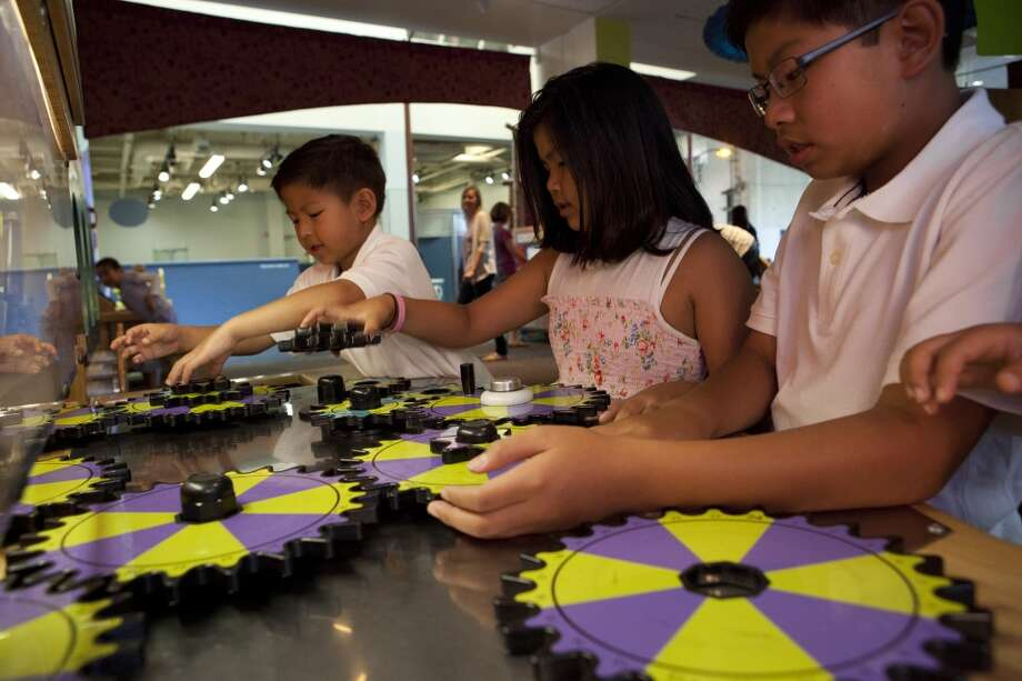 Children work on gears as part of the traveling exhibition Secrets of Circles. It arrives at Stepping Stones Museum for Children in Norwalk, Conn., on Saturday, Sept. 28, 2013, for a three-month run. There will be plenty of activities for all ages. For more information, visit steppingstonesmuseum.org. Photo: Jason Lew Photo: Contributed Photo