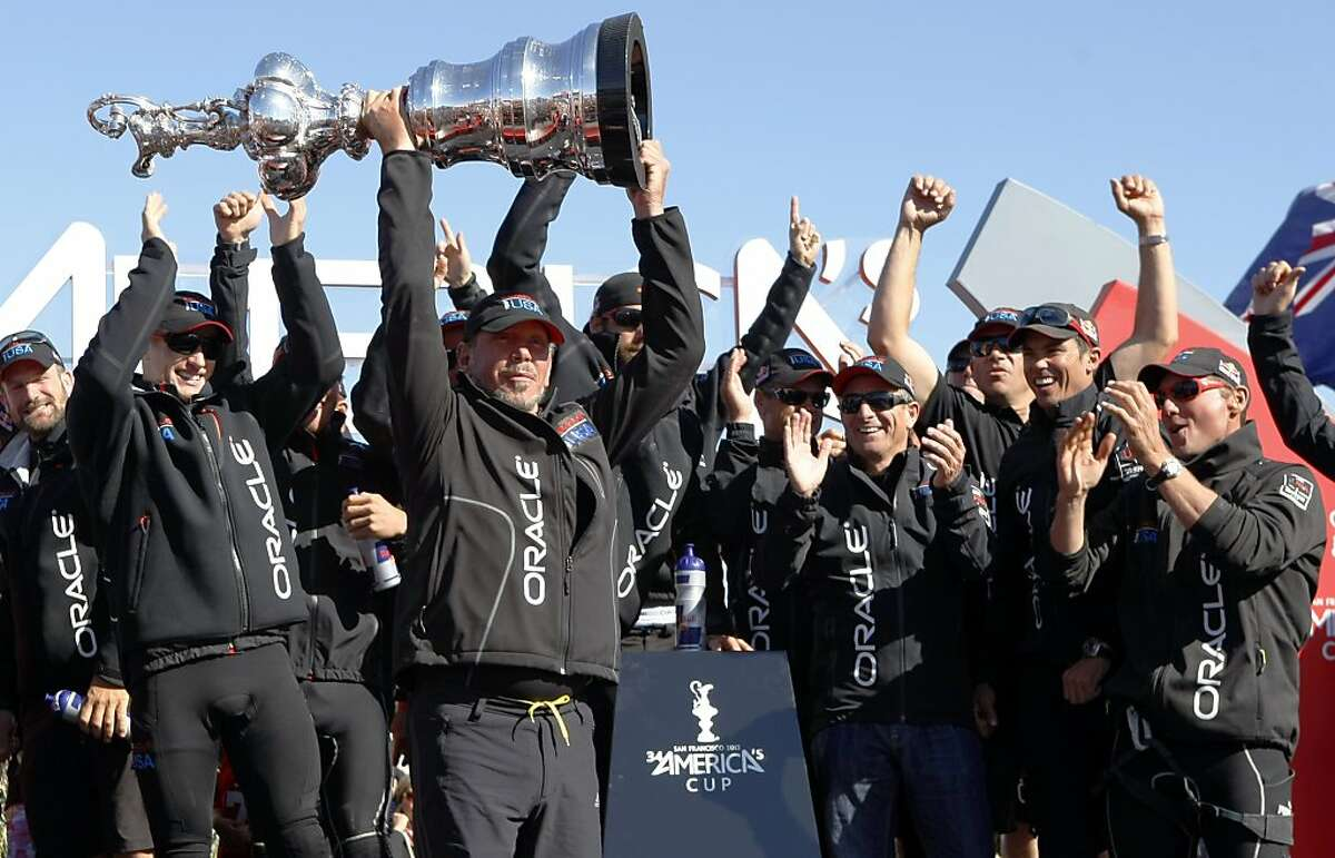 Oracle Team USA owner Larry Ellison hoists the trophy after winning the 34th America's Cup on Wednesday, September 25, 2013 in San Francisco, Calif.