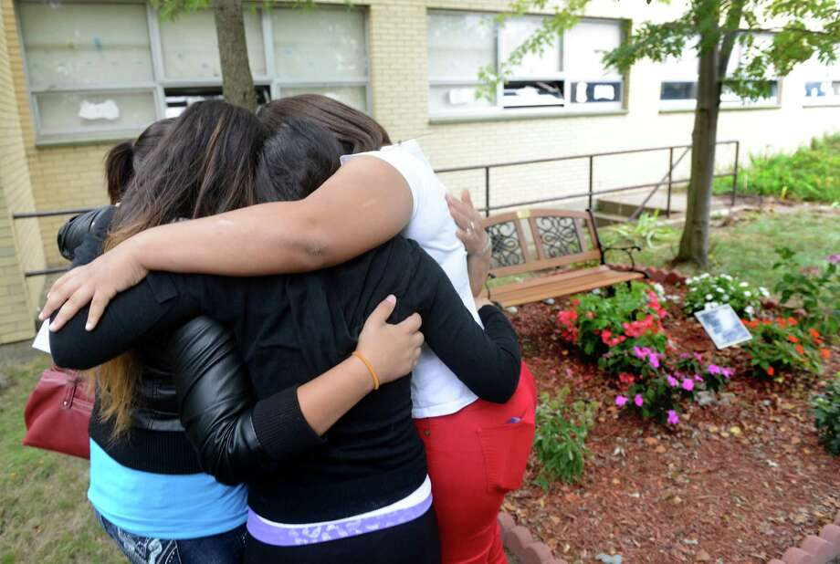 Digna Pacheco, Tania's mother, Carmita Zuniga, Tania's sister, and Teresa Zepeda, Mayte Figueroa and Amy White embrace Friday, Sept. 27, 2013 next to the Tania Zuniga Memorial in the Blackham School courtyard.  The three girls attended Blackham School with Tania who died unexpectedly over the summer and returned to the school to pay tribute to their friend by establishing a garden in her memory. Photo: Autumn Driscoll / Connecticut Post
