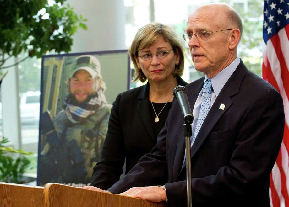 Navy SEAL Brian Bill's parents, Patricia and Michael Parry, stand beside a photo of their son as they speak during a ceremony at Government Center in Stamford, Conn., on Friday, Sept. 27, 2013, to rename a portion of Washington Blvd. in honor of their son, who was killed in Afghanistan in 2011. Photo: Lindsay Perry / Stamford Advocate