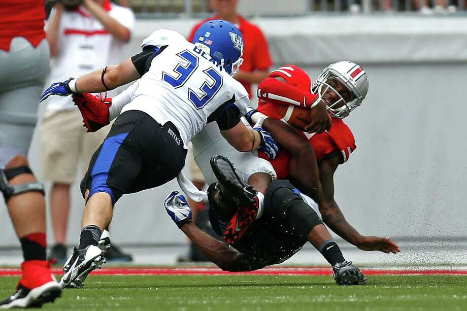 COLUMBUS, OH - AUGUST 31:  Braxton Miller #5 of the Ohio State Buckeyes is sacked by Khalil Mack #46 and Blake Bean #33, both of the Buffalo Bulls, during the third quarter on August  31, 2013 at Ohio Stadium in Columbus, Ohio. Ohio State defeated Buffalo 40-20. Photo: Kirk Irwin, Getty Images / 2013 Getty Images North America