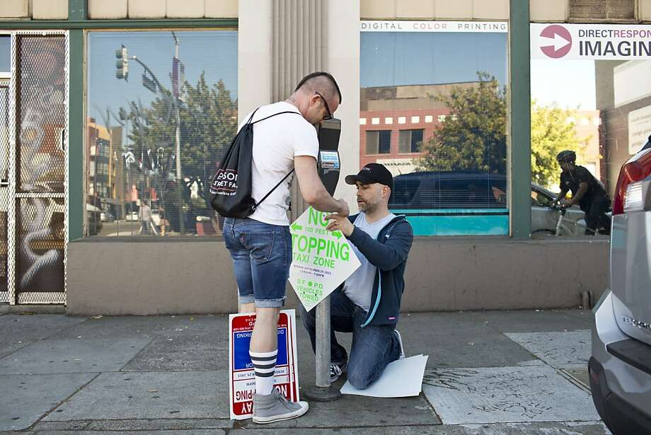 Folsom Street Fair staffers Demetri Moshoyannis and Patrick Finger post no-parking signs Thursday. Photo: Jason Henry, Special To The Chronicle