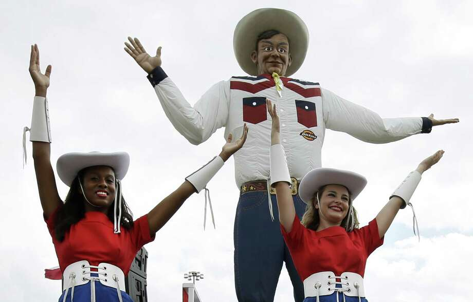 Kilgore College Rangerettes Cera Taylor, left, and Rachel Meents, right, pose in front of Big Tex after an official ceremony welcoming back the structure to the State Fair of Texas, Friday, Sept. 27, 2013, in Dallas. The fair runs Sept. 27, through Oct. 20. (AP Photo/Tony Gutierrez) Photo: Tony Gutierrez, Associated Press / AP
