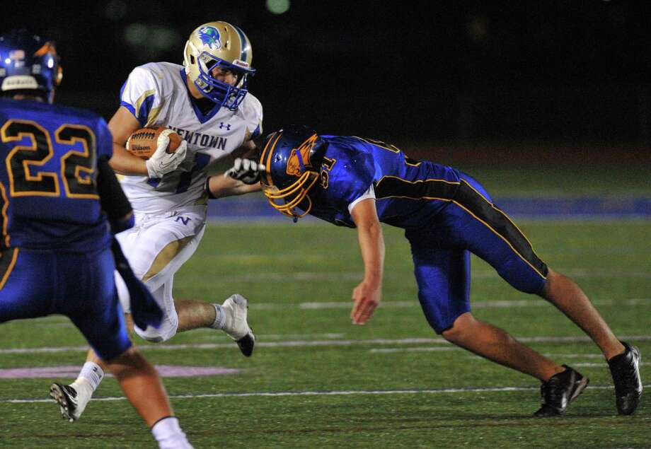 Newtown running back Cooper Gold runs as Brookfield defender Matthew Biondi (51) attempts a tackle in the SWC high school football game between Brookfield and Newtown at Brookfield High School in Brookfield, Conn. on Friday, Sept. 27, 2013. Photo: Tyler Sizemore / The News-Times