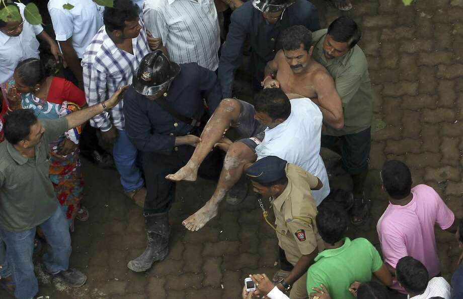 Rescue workers carry an injured man from the rubble of the Babu Genu Market building in Mumbai, India. Friday morning's was the fifth deadly collapse this year in or near Mumbai. Photo: Rajanish Kakade / Associated Press