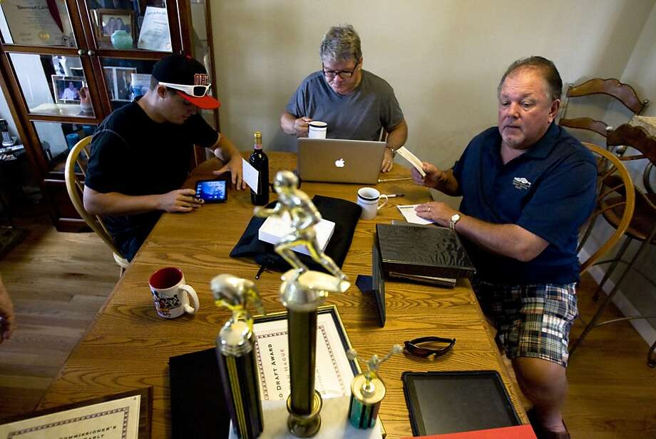 Shane Murchison (left), Pete Murchison and Tom Barentston prepare for the Lou & Robbo league draft last month in Fremont. Photo: Raphael Kluzniok, The Chronicle