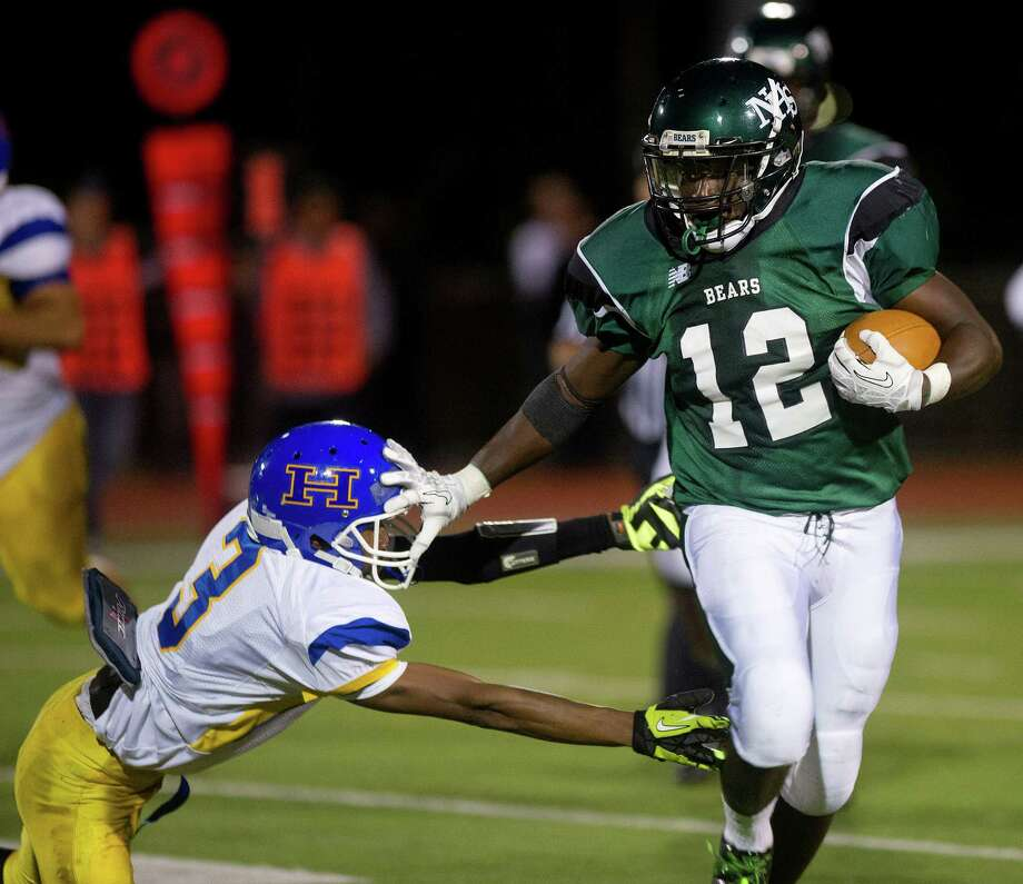 Norwalk's Clifford Joseph carries the ball as Harding's Terrance Rogers tries to tackle during Friday's football game at Norwalk High School on Sept. 27, 2013. Photo: Lindsay Perry / Stamford Advocate