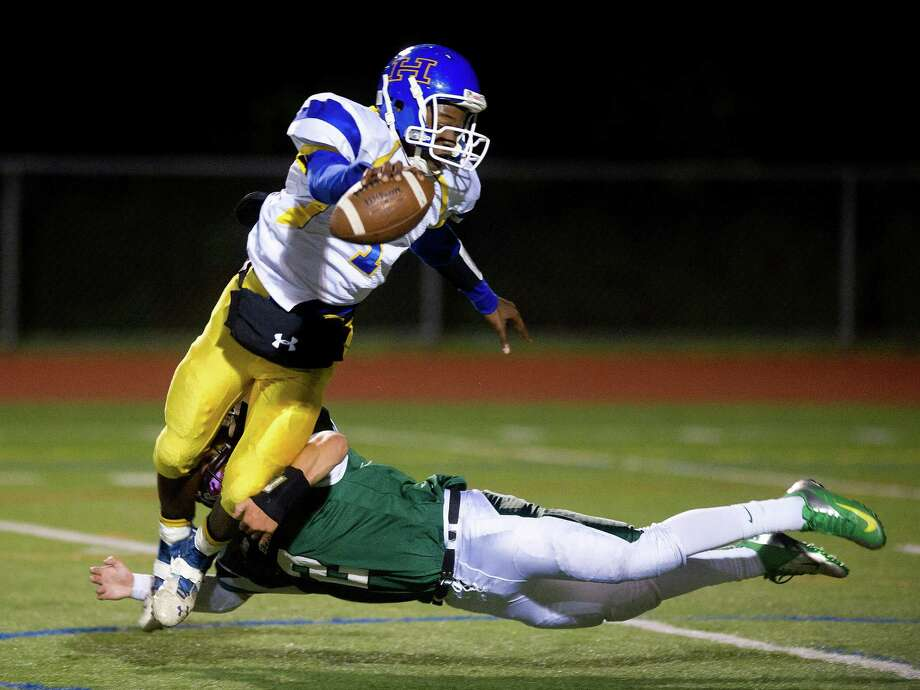 Norwalk's Harrison Hefferan dives to tackle Harding's Christian Hopkins during Friday's football game at Norwalk High School on Sept. 27, 2013. Photo: Lindsay Perry / Stamford Advocate