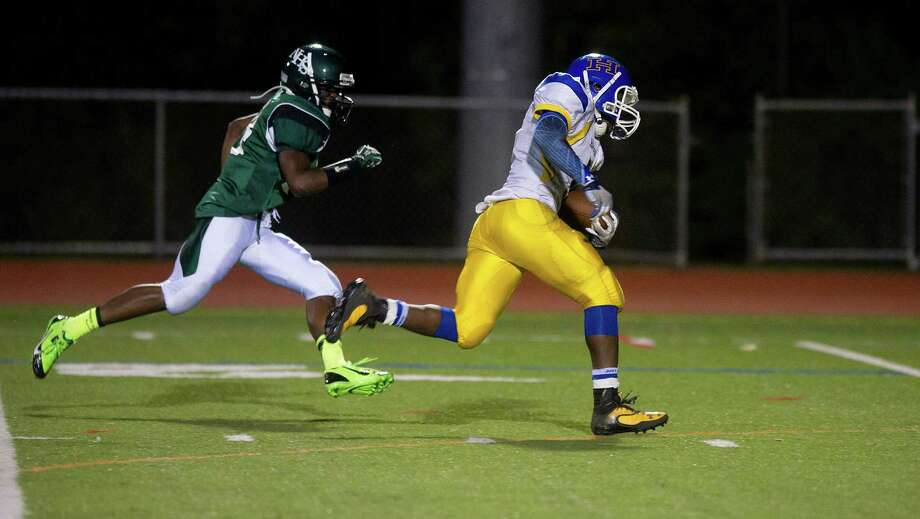 Harding's Reggie David scores a touchdown as he is chased by Norwalk's Anthony Wooten during Friday's football game at Norwalk High School on Sept. 27, 2013. Photo: Lindsay Perry / Stamford Advocate