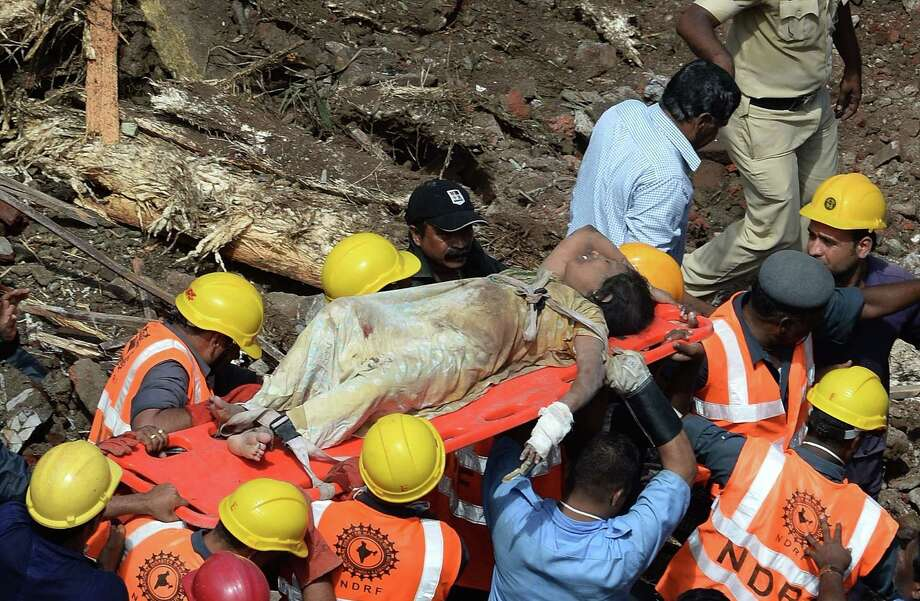 Firefighters bring out a female survivor from the rubble at the site of a building collapse in Mumbai on September 27, 2013. A five-storey residential block collapsed in Mumbai at daybreak killing at least three people and leaving up to 70 feared trapped inside, in the latest building disaster to hit India's financial capital  AFP PHOTO/Indranil MUKHERJEEINDRANIL MUKHERJEE/AFP/Getty Images Photo: INDRANIL MUKHERJEE / AFP