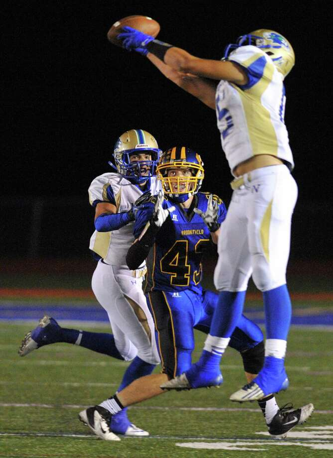 Brookfield's Daniel Jackson (43) watches as Newtown's Julian Moore rises up for an interception in the SWC high school football game between Brookfield and Newtown at Brookfield High School in Brookfield, Conn. on Friday, Sept. 27, 2013. Photo: Tyler Sizemore / The News-Times