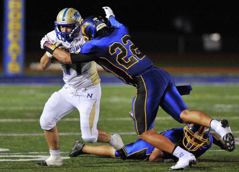 Newtown's Cooper Gold runs as Brookfield defender Liam Clancy attempts a tackle in the SWC high school football game between Brookfield and Newtown at Brookfield High School in Brookfield, Conn. on Friday, Sept. 27, 2013. Photo: Tyler Sizemore / The News-Times