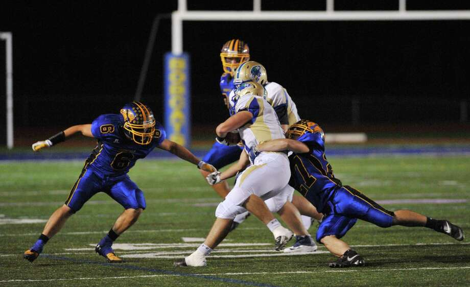 Brookfield defenders Nick Seis (6) and Matthew Melby (27) team up for a tackle on Newtown's Cooper Gold in the SWC high school football game between Brookfield and Newtown at Brookfield High School in Brookfield, Conn. on Friday, Sept. 27, 2013. Photo: Tyler Sizemore / The News-Times