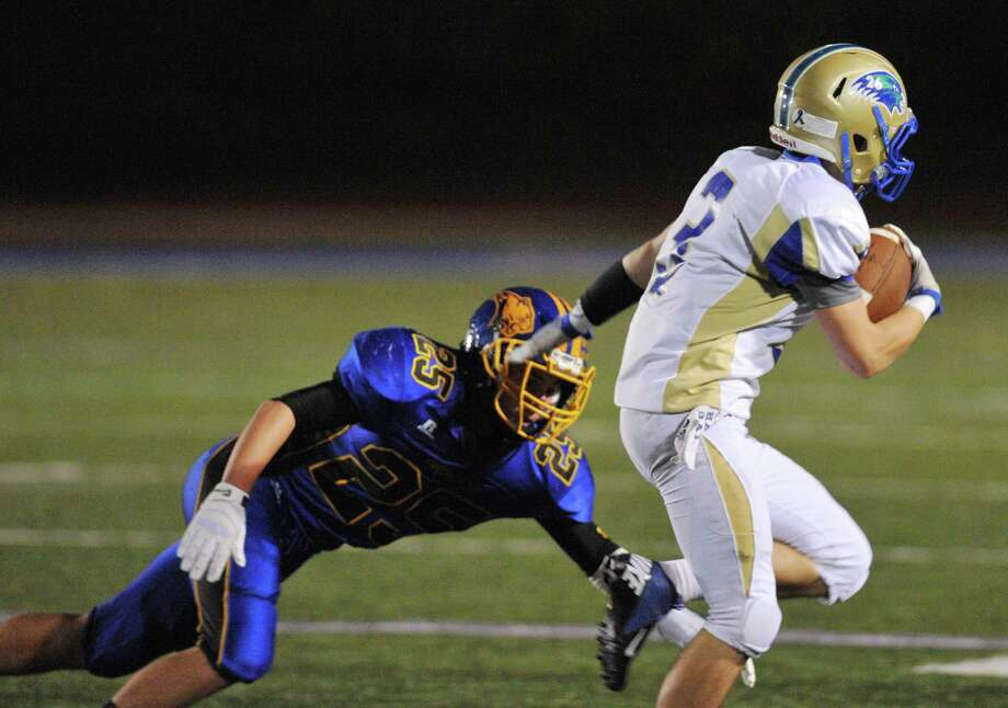 Brookfield defender Gabe Pompette attempts to tackle Newtown wide receiver Troy Frangione in the SWC high school football game between Brookfield and Newtown at Brookfield High School in Brookfield, Conn. on Friday, Sept. 27, 2013. Photo: Tyler Sizemore / The News-Times
