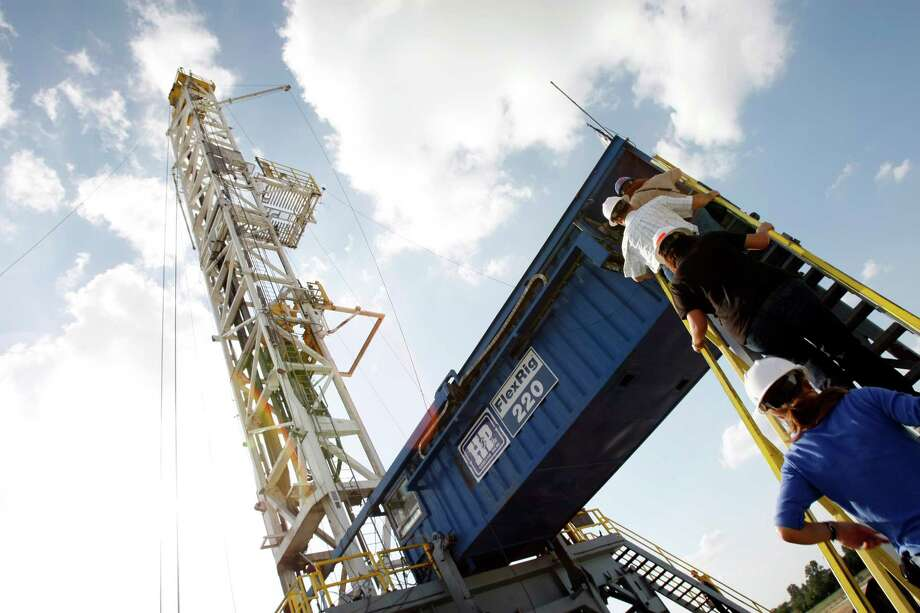 A Devon Energy flex-drilling rig rises toward the clouds near Denton. Devon, based in Oklahoma City, says the proposed partnership will have a 20 percent stake in the oil and gas company's mainstream business. Photo: Kevin Fujii, Staff / Houston Chronicle