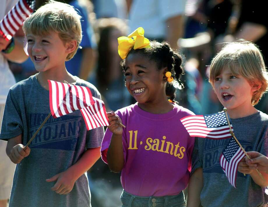 All Saints Episcopal School kindergartners Nash Bergfeld, 5, Maddie Daniel, 5, and Finn Delaney, 5, American flags as the Texas Wounded Warriors arrive during a special program with the Texas Wounded Warriors organization at their school in Tyler, Texas on Friday, Sept. 27, 2013. The 6th annual Texas Wounded Warriors celebrity pro-am raises money for Hope for the Warriors, a national nonprofit organization that assists wounded U.S. service members, their families and families of the fallen. Photo: Sarah A. Miller, Associated Press / Tyler Morning Telegraoh