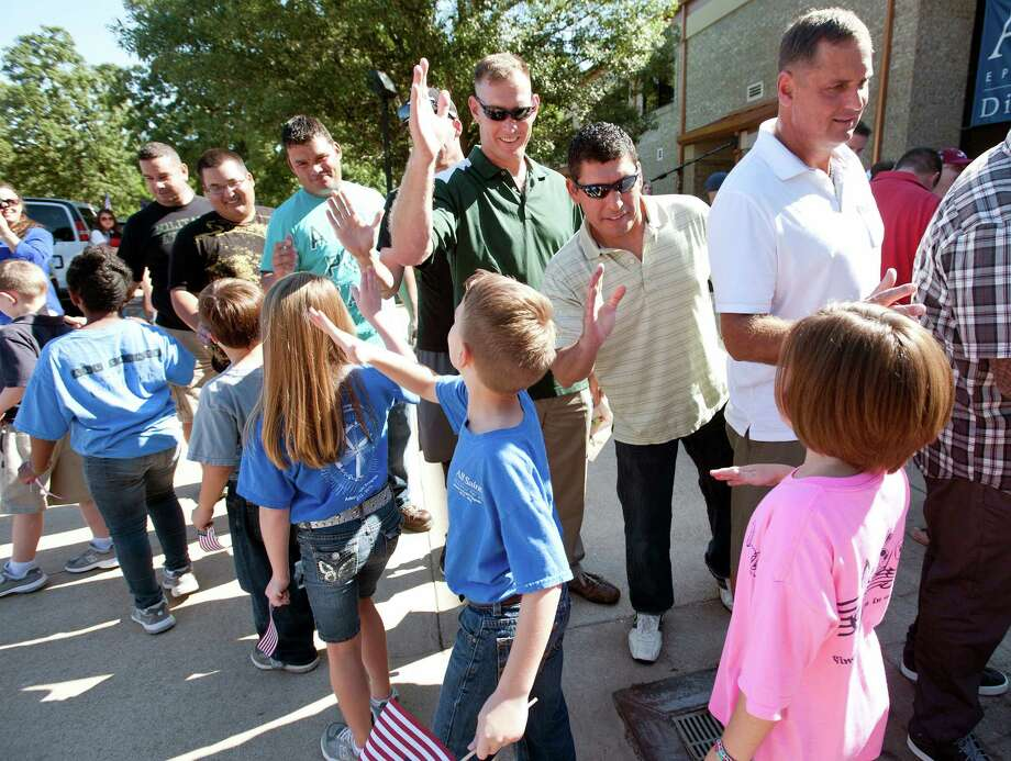 All Saints Episcopal School students high-five wounded service members during a special program with the Texas Wounded Warriors organization at their school in Tyler, Texas on Friday, Sept. 27, 2013. Photo: Sarah A. Miller, Associated Press / Tyler Morning Telegraoh