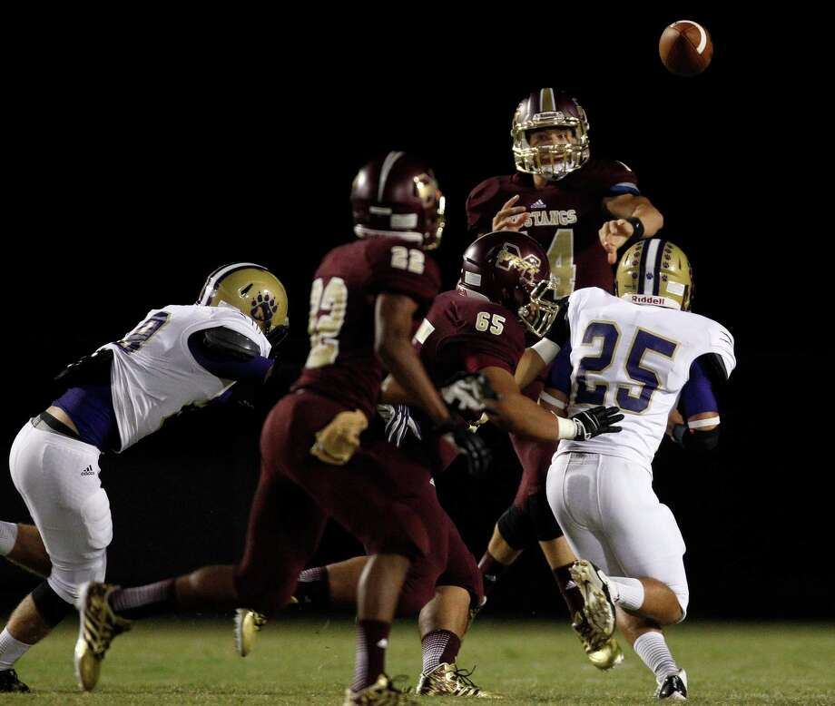 Magnolia West quarterback Troy Logan passes the ball to teammate Adrian Thomas (22) during the first half of a high school football game against Montgomery, Friday, September 27, 2013 at Mustang Stadium in Magnolia. Photo: Eric Christian Smith, For The Chronicle