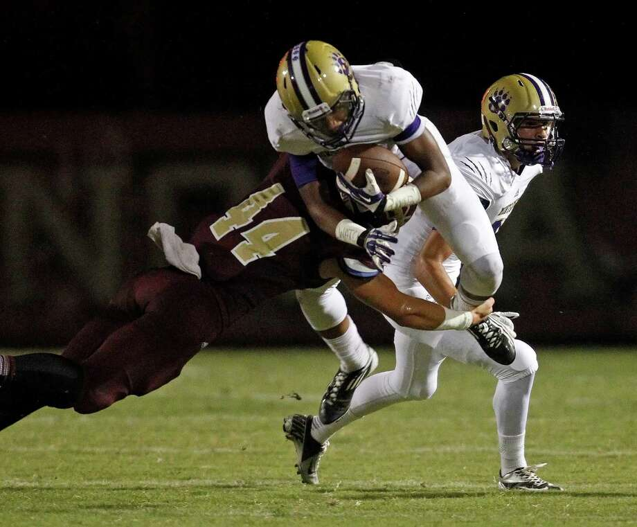 Montgomery's Ken'dre Howard, right, is tackled by Magnolia West's Will Hicks during the first half of a high school football game, Friday, September 27, 2013 at Mustang Stadium in Magnolia. Photo: Eric Christian Smith, For The Chronicle