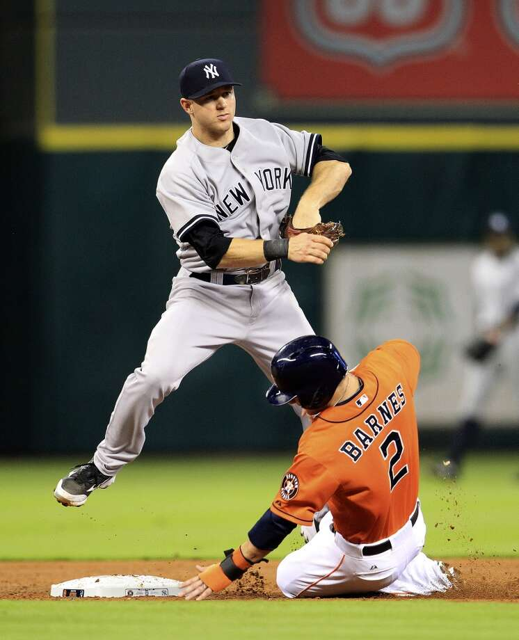 Yankees third baseman David Adams (45)  jumps over Astros center fielder Brandon Barnes (2) as he forces him out at second. Photo: Karen Warren, Houston Chronicle