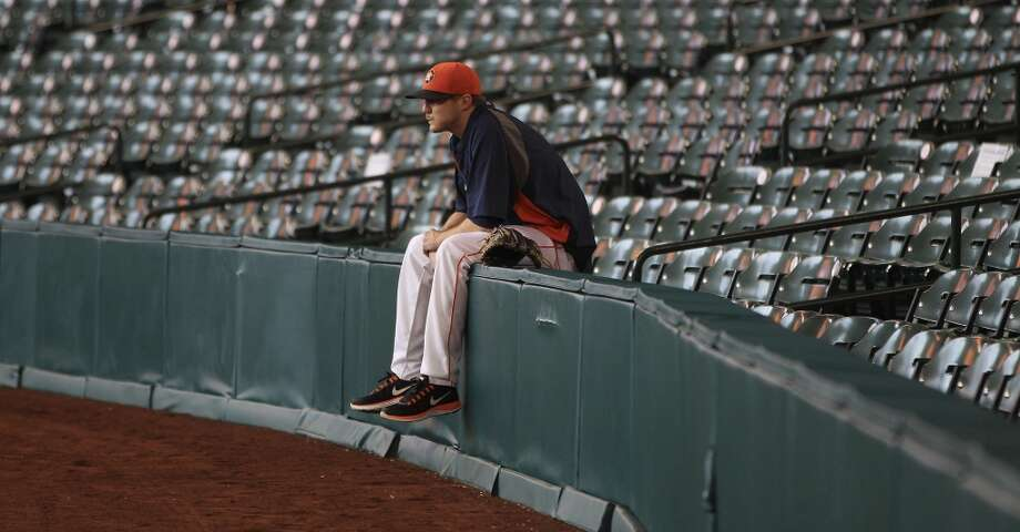 Astros relief pitcher Paul Clemens (56) sits on the fence between the seats and the warning track before the start of batting practice. Photo: Karen Warren, Houston Chronicle