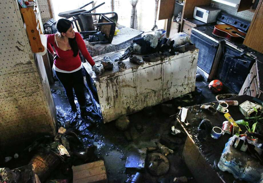 Sonia Marquez of the Colorado Immigrant Rights Coalition looks for keepsakes inside one of the wrecked homes in Evans, Colo.