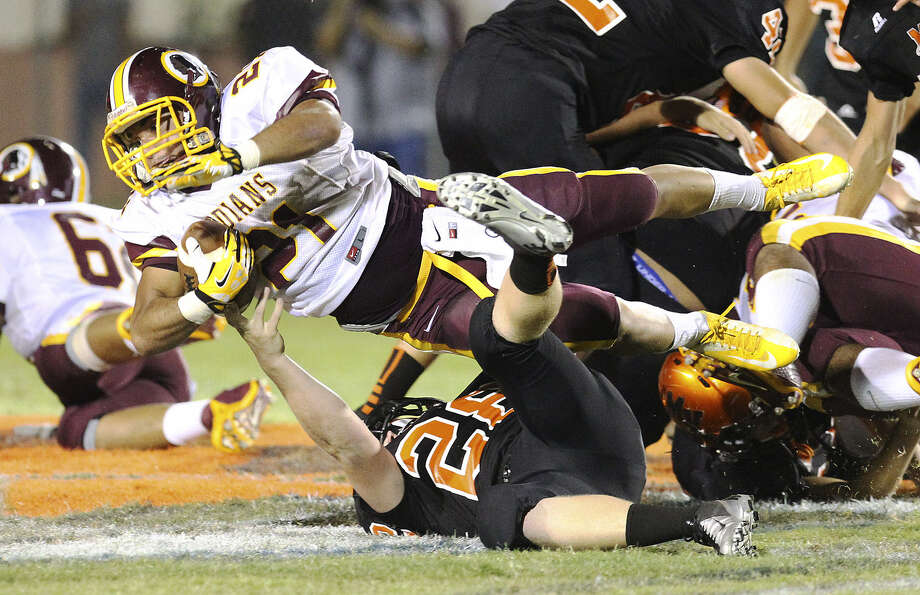 Harlandale's Nicholas Martinez (top) dives over Medina Valley's Jonathan Groff during Friday's game at Panther Stadium in Castroville. Martinez rushed for 88 yards and scored a touchdown. Photo: Kin Man Hui / San Antonio Express-News