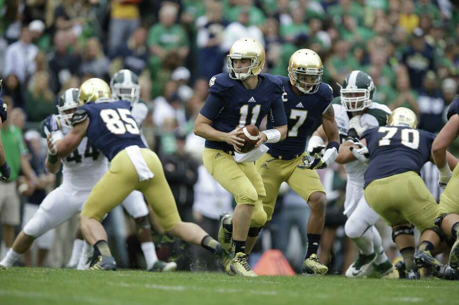 Notre Dame quarterback Tommy Rees has made opposing defenses pay for stacking the line to stop the run. Photo: Michael Conroy / Associated Press