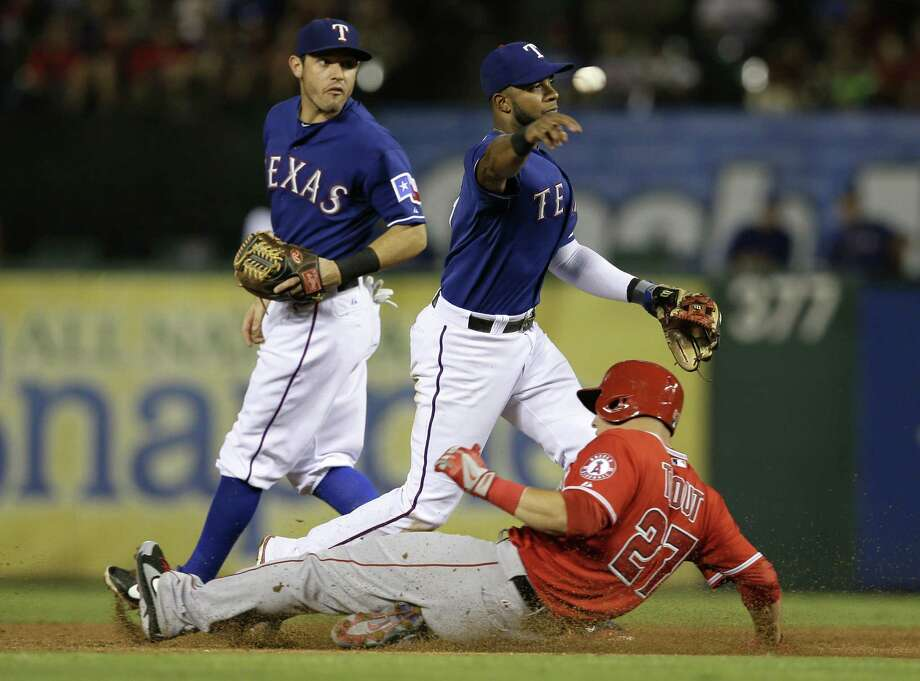 Rangers shortstop Elvis Andrus throws to first over the Angels' Mike Trout to complete a double play in the third inning. Photo: Tony Gutierrez / Associated Press