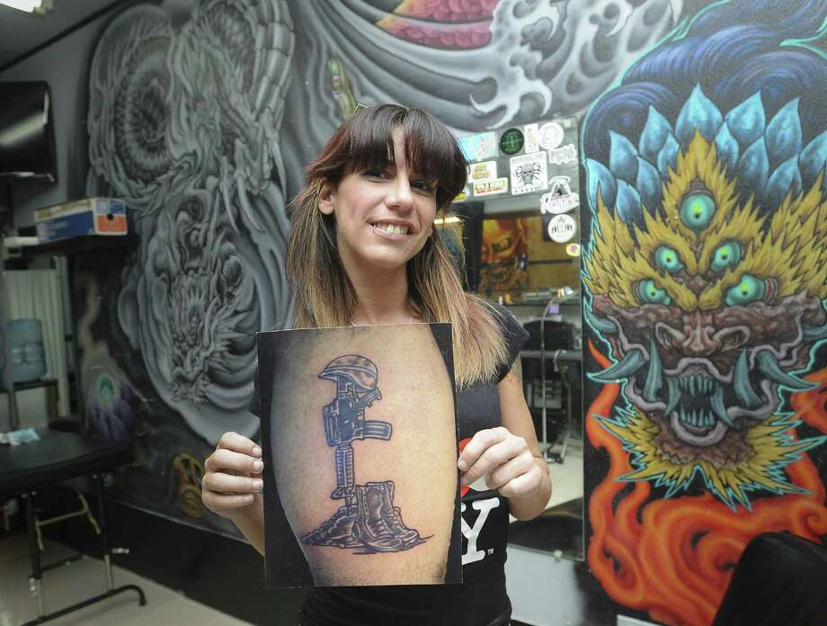 """Sonia Anderson, tattoo artist at Adrenaline Tattoos and Body Piercing, displays a photograph of an """"In memory"""" tattoo that is one of the more popular inkings that she has applied to military personnel. Photo: Photos By Billy Calzada / San Antonio Express-News"""