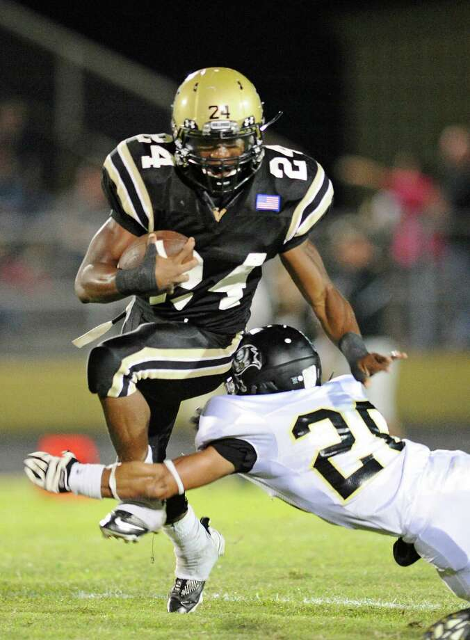 Nederland's Kendrick Hopkins (24) tries to elude Vidor's Josh Clayton (20) during first quarter action in Friday nights game at Bulldog Stadium.