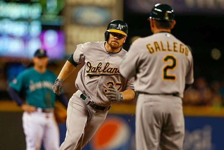 Brandon Moss is congratulated by third-base coach Mike Gallego after his three-run homer in the first inning. Photo: Otto Greule Jr, Getty Images