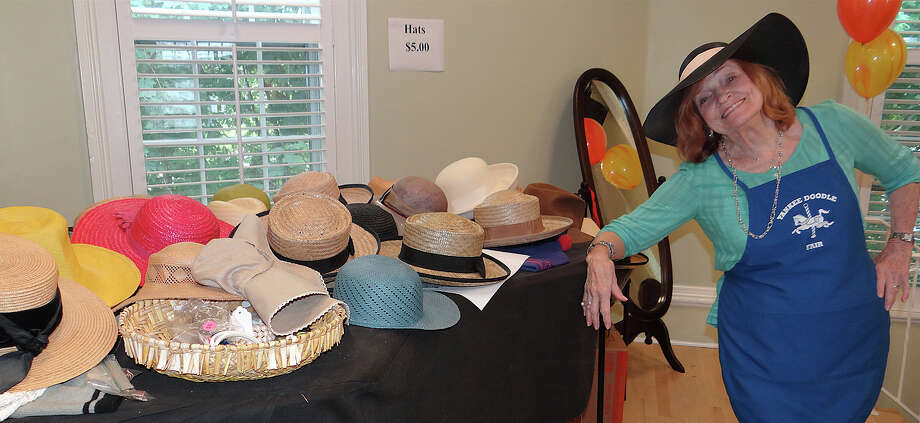 Westport Woman's Club volunteer Jo Ann Pickholtz at the display of hats available at the club's annual tag sale Friday. Photo: Mike Lauterborn / Westport News contributed