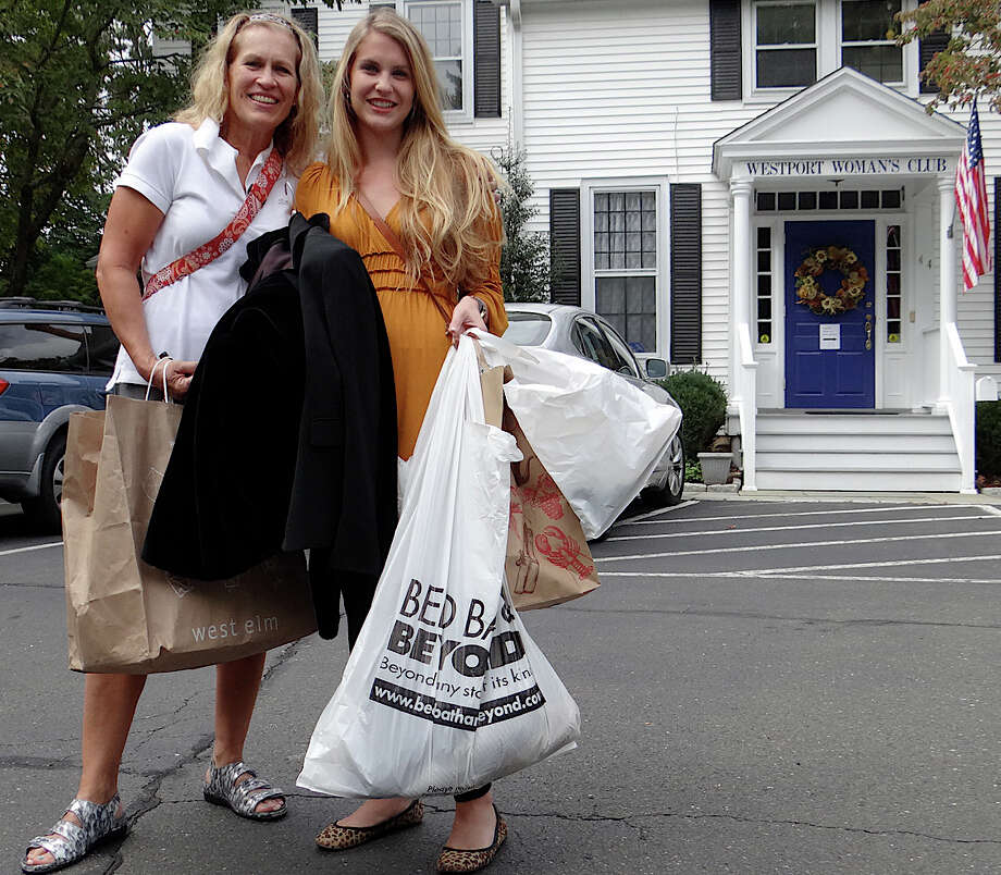 Jude and Brett Healy of Fairfield with purchases Friday from the Westport Woman's Club's annual tag sale. Photo: Mike Lauterborn / Westport News contributed