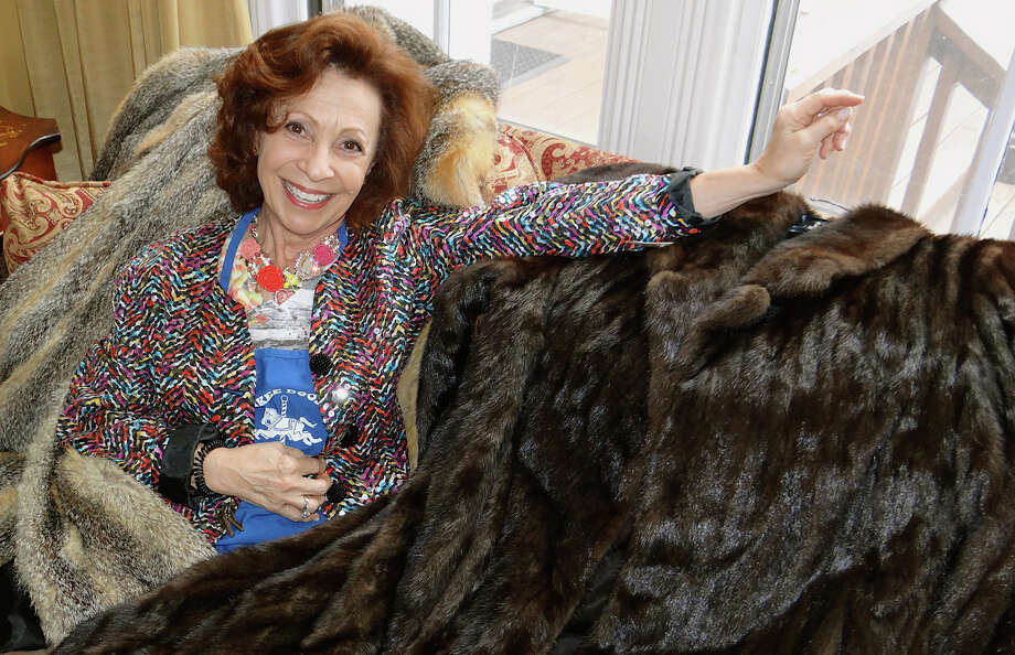 Volunteer Vivian Rosenberg show off fur coats at the Westport Woman Club's clothing tag sale on Friday. Photo: Mike Lauterborn / Westport News contributed