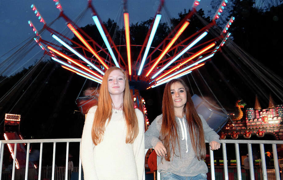 Fairfielders Bree Fields, 13, and Nathalia Curi, 14, in front of the Musical Chairs ride at the Friday night opening of the Dwight School fair.  FAIRFIELD CITIZEN, CT 9/27/13 Photo: Mike Lauterborn / Fairfield Citizen contributed