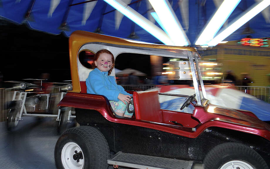 Bridget Carey, 6, rides a Hampton dune buggie at the opening night of the Dwight School fair Friday.  FAIRFIELD CITIZEN, CT 9/27/13 Photo: Mike Lauterborn / Fairfield Citizen contributed