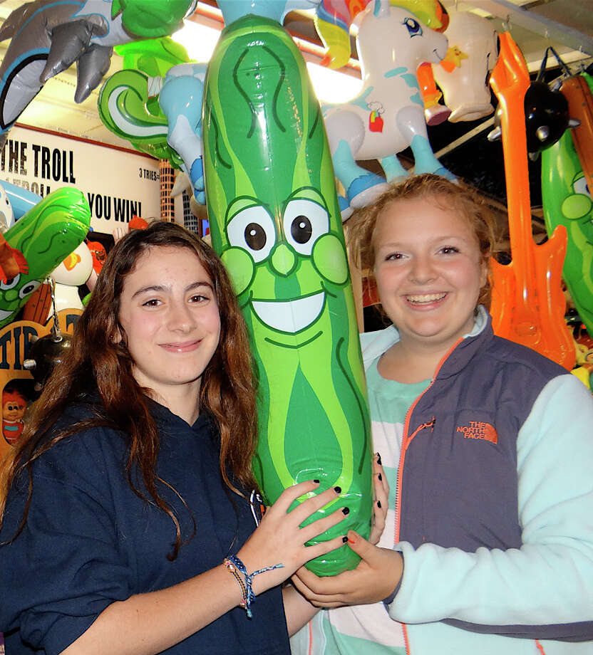 Allison Gentry and Maiya Urquhart, both14, with the inflatable pickle they won in the Tip the Troll game at the opening night of the Dwight School fair Friday.  FAIRFIELD CITIZEN, CT 9/27/13 Photo: Mike Lauterborn / Fairfield Citizen contributed