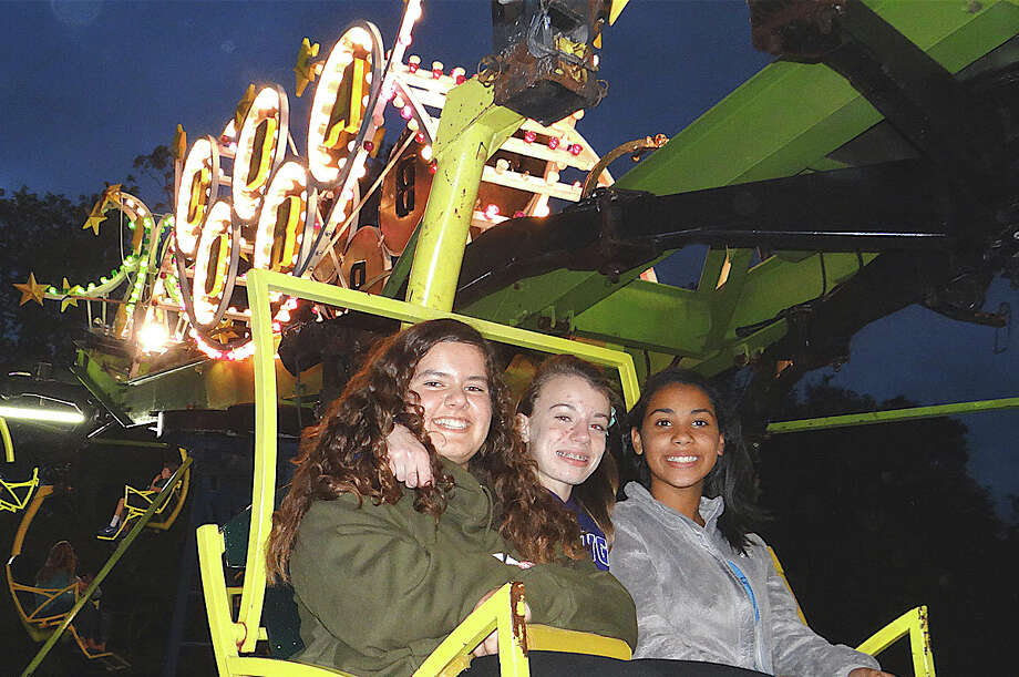 India Mutchnick, 13; Emma Powell, 13, and Charlotte Grens, 12, ride The Cobra at Dwight School fair's opening night Friday.  FAIRFIELD CITIZEN, CT 9/27/13 Photo: Mike Lauterborn / Fairfield Citizen contributed