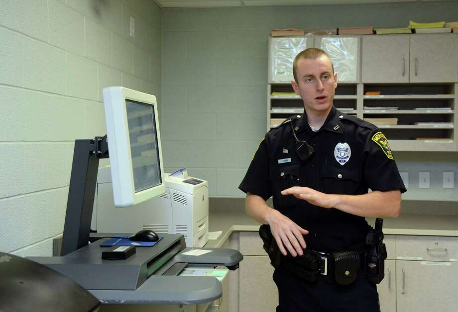 Officer Brendan Fearon explains how the AFIS machine eliminates the use of ink during criminal arrests Saturday, Sept. 28, 2013 during an open house to show off renovations to The Monroe Police Department. Photo: Autumn Driscoll / Connecticut Post