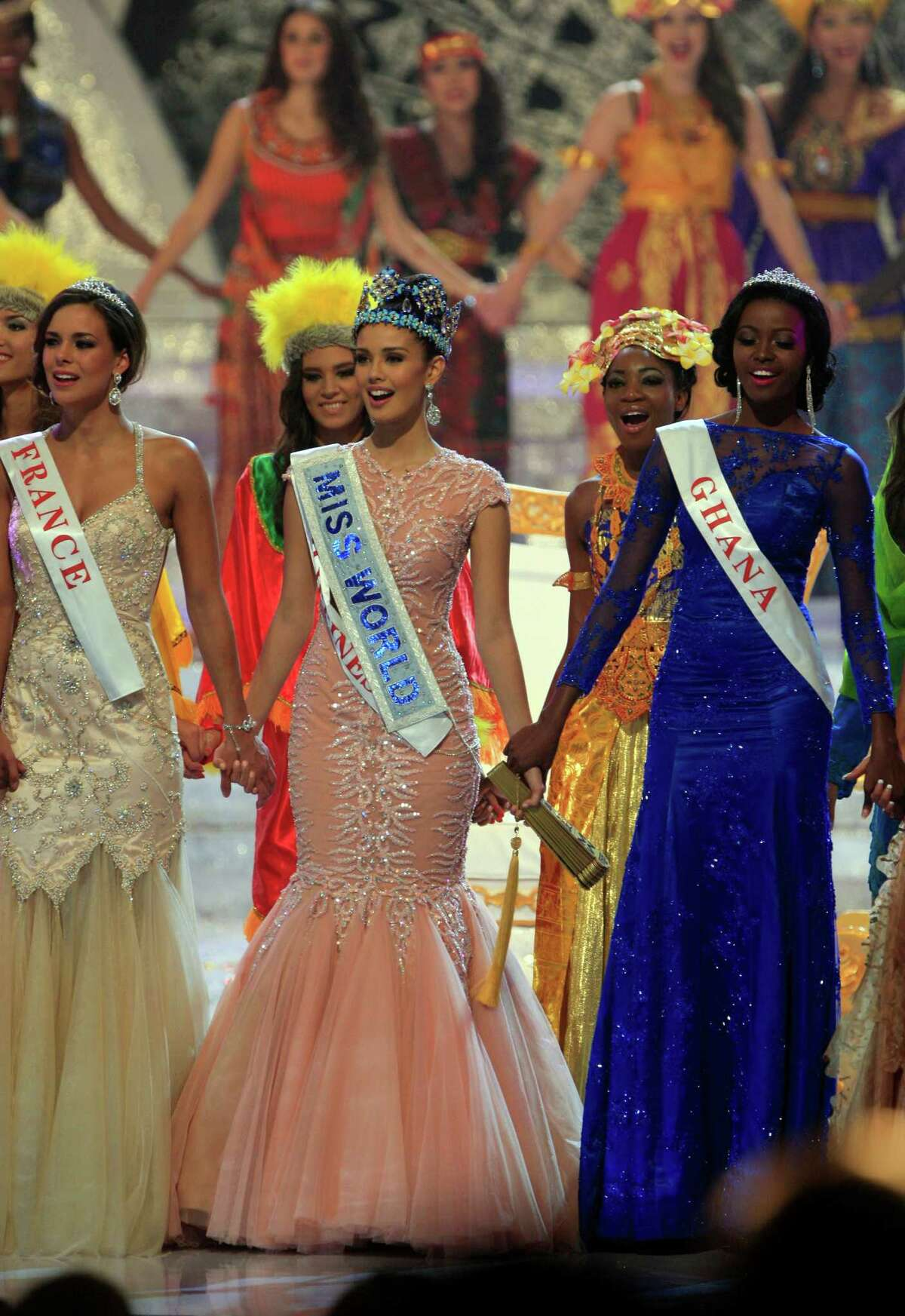 Newly crowned Miss World 2013 Megan Young of the Philippines, center, hold hands with second runner-up Miss France Marine Lorpheline, left, and third runner-up Miss Ghana Carranza Naa Okailey Shooter, right, during the grand final of the pageant in Nusa Dua, Bali, Indonesia, Saturday, Sept. 28, 2013. Miss Philippines, Megan Young, was crowned Miss World on Saturday amid tight security on Indonesia's resort island of Bali, where the contest's final round was moved following protests by Muslim hardliner groups.