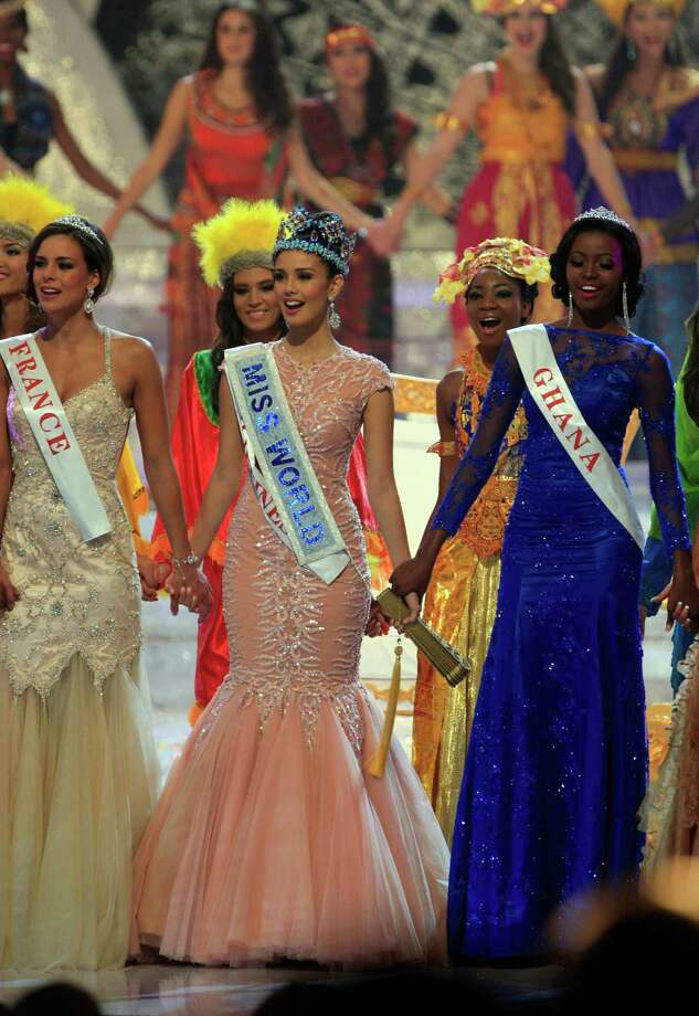 Newly crowned Miss World 2013 Megan Young of the Philippines, center, hold hands with second runner-up Miss France Marine Lorpheline, left, and third runner-up Miss Ghana Carranza Naa Okailey Shooter, right, during the grand final of the pageant in Nusa Dua, Bali, Indonesia, Saturday, Sept. 28, 2013. Miss Philippines, Megan Young, was crowned Miss World on Saturday amid tight security on Indonesia's resort island of Bali, where the contest's final round was moved following protests by Muslim hardliner groups. Photo: AP