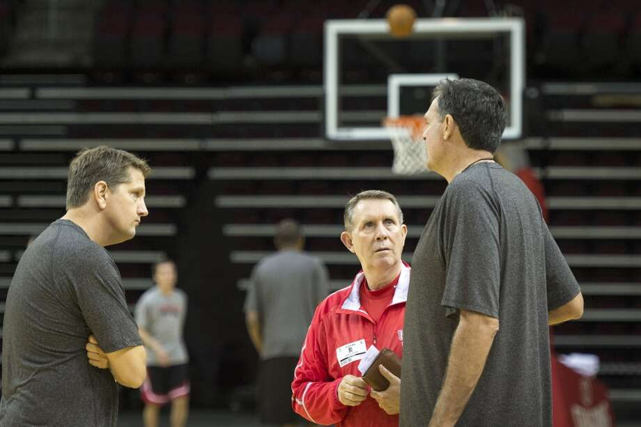 University of Houston basketball coach James Dickey, facing, talks with Rockets head coach Kevin McHale, right, and assistant coach Chris Finch. Photo: Smiley N. Pool, Houston Chronicle