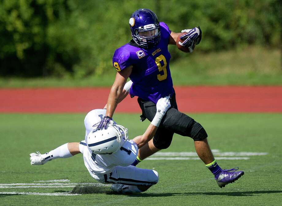 Westhill's Dennis Hart-Lima carries the ball as he tries to avoid a tackle by Staples' Bobby Jacowleff during Saturday's football game in Stamford, Conn., on Sept. 28, 2013. Photo: Lindsay Perry / Stamford Advocate