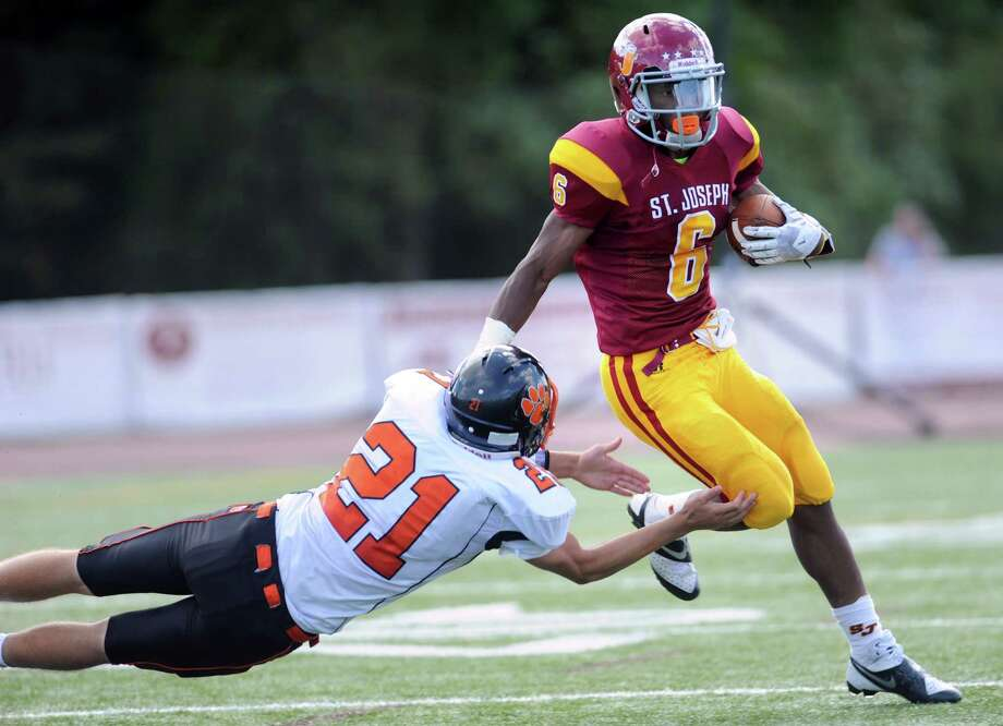 St.Joseph's Mufasa Abdul-Basir avoids a tackle by Ridgefield's Daniel Peckham Saturday, Sept. 28, 2013 during their game at St. Joseph High School in Trumbull, Conn. Photo: Autumn Driscoll / Connecticut Post