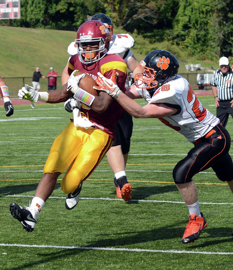 St.Joseph's Mufasa Abdul-Basir shrugs off Ridgefield's James Hesemeyer on his way to a touchdown Saturday, Sept. 28, 2013 during their game at St. Joseph High School in Trumbull, Conn. Photo: Autumn Driscoll / Connecticut Post