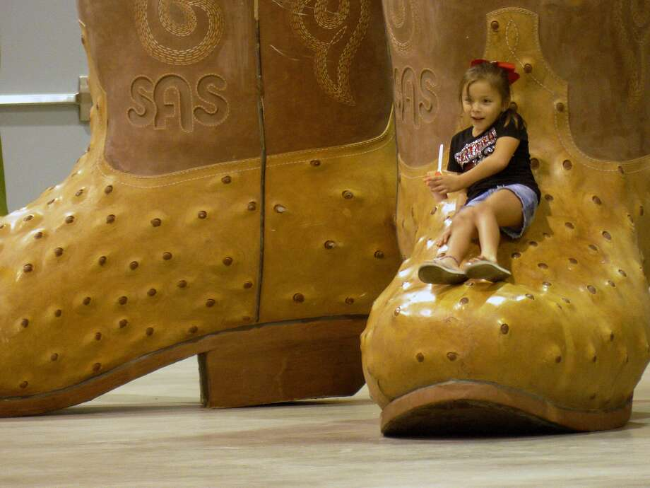 Gabrielle Lastovita, 7, enjoys herself on a giant pair of cowboy boots during the San Antonio Stock Show & Rodeo Bar-B-Que Cook-Off & Festival on Saturday, Sept. 28, 2013. Photo: Billy Calzada, San Antonio Express-News / San Antonio Express-News